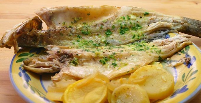 lubina al horno con patatas y cebolla. Un delicioso pescado que, con este toque, quedará espectacular